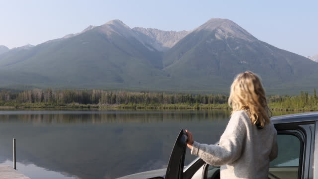 woman exits vehicle door to look at mountain view - banff stock videos & royalty-free footage