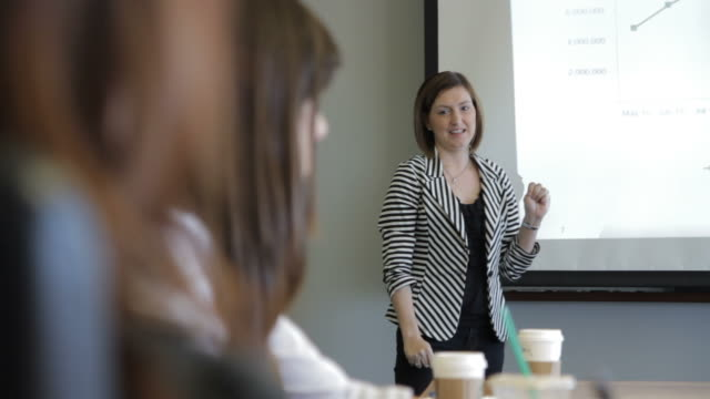woman explaining graph during presentation - strategia di vendita video stock e b–roll
