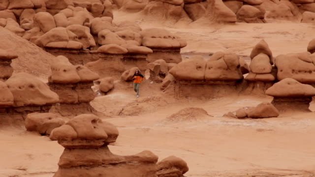 woman explores giant stone mushrooms utah's goblin valley state park - entrada stock videos and b-roll footage