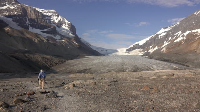 Woman explores hikes melting Athabasca Glacier Jasper National Park Alberta Canada