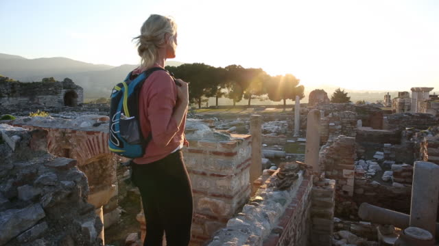 woman explores monument ruins, walks through rubble - old ruin stock videos & royalty-free footage