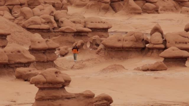 Woman explores sandstone mushrooms Goblin Valley State Park Utah