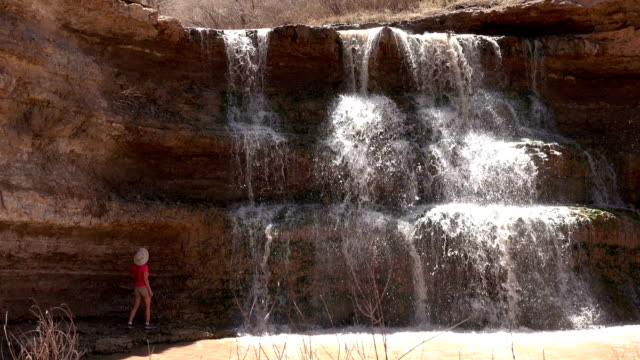 Woman explores Vermillion Falls waterfall Browns Park National Wildlife Refuge Colorado desert