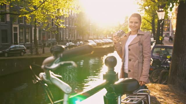 vidéos et rushes de femme explorant amsterdam, restant à côté du canal, prenant des photos avec le rétro de vieille école, appareil-photo analogique de cru - photographe