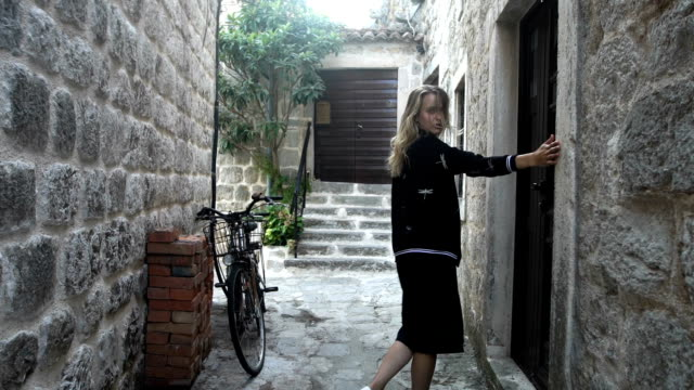 woman exploring city. smiling to a camera and posing - stone wall stock videos and b-roll footage