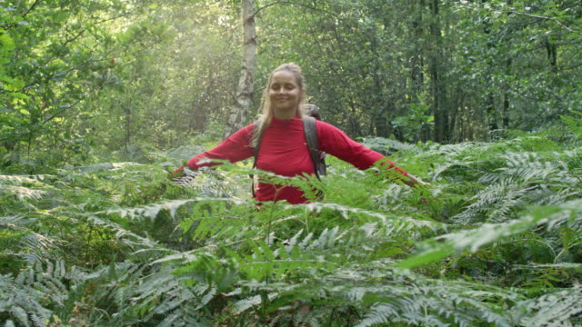 Woman exploring glade with ferns. Using compass