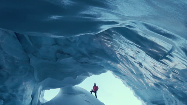 stockvideo's en b-roll-footage met vrouw verkennen ice cave - exploration