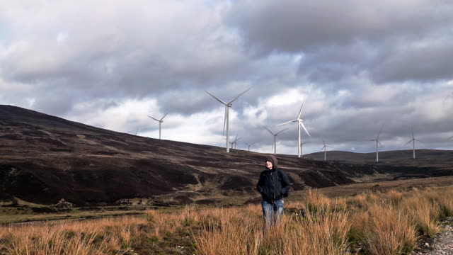 woman exploring near renewable energy wind turbines - carbon footprint stock videos and b-roll footage