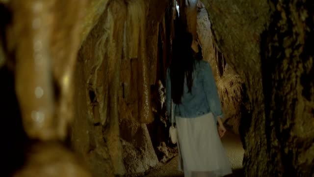 Kvinna att utforska grottan