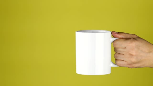 woman extending a ceramic cup inwards to the frame - yellow background stock videos & royalty-free footage