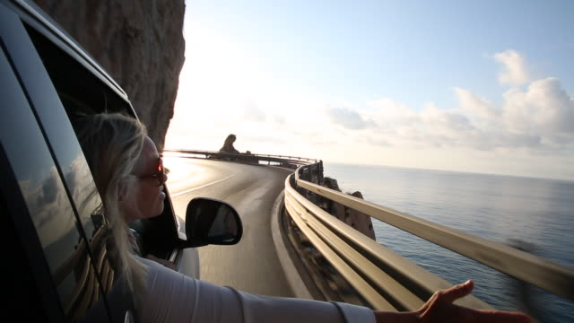 woman extends arm from car window, along coastal drive - ドライブ旅行点の映像素材/bロール