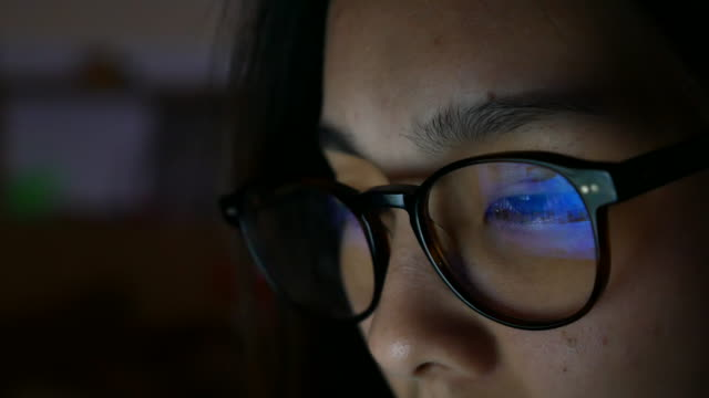 Woman eye looking monitor at night, surfing Internet