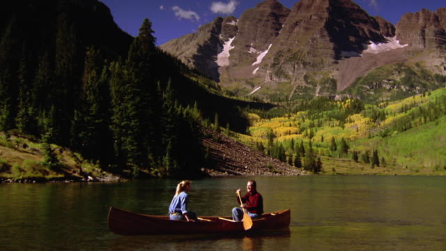 Woman facing man rowing canoe in lake / pine trees + mountains in background / Aspen, Colorado