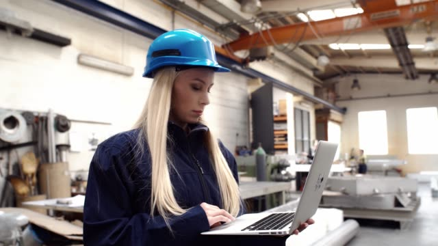 Woman factory worker in a hard hat is using a laptop computer with an engineering software