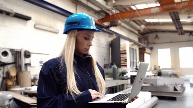 Vrouw fabrieksarbeider in een helm is met behulp van een laptopcomputer met een engineeringsoftware