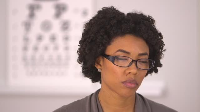 vídeos de stock e filmes b-roll de woman falling asleep at optometrist office - só uma mulher de idade mediana