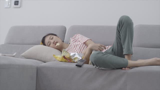 woman falling asleep lying on sofa and watching tv, seoul, south korea - sofa stock videos & royalty-free footage