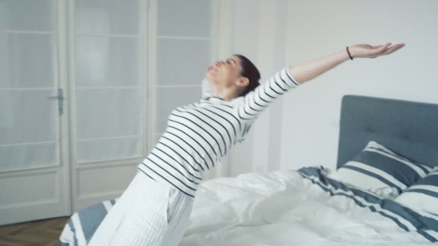 woman falling backward onto bed - comfortable stock videos & royalty-free footage