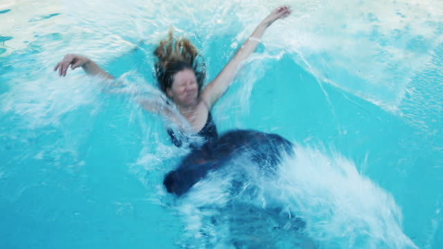 woman falling into pool wearing long dress - kleid stock-videos und b-roll-filmmaterial
