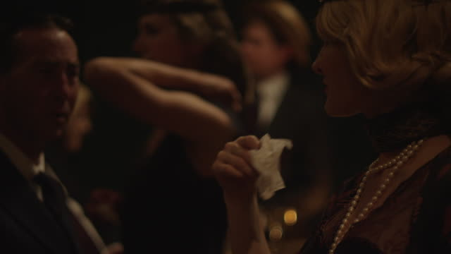 woman fans face with napkin at a party - serviette stock-videos und b-roll-filmmaterial