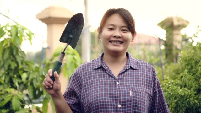 woman farmer in nature scene standing looking camera and smiling hand shovel