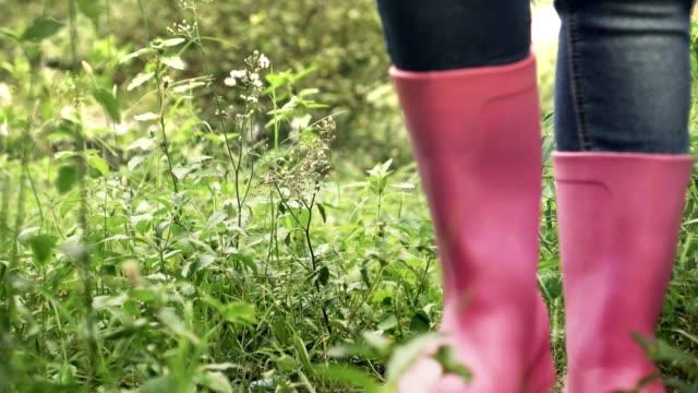 woman farmer walking in green grass close up low shot pink shoe boot