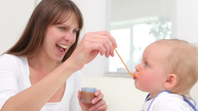 vídeos de stock, filmes e b-roll de woman feeding a baby - comida de bebê