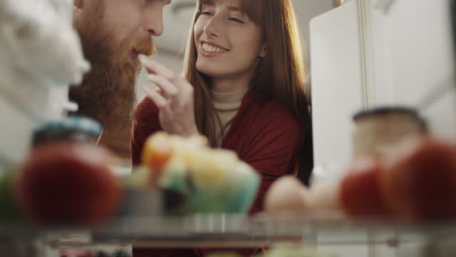 woman feeding boyfriend with fruit taken from refrigerator - freshness stock videos & royalty-free footage