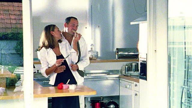vídeos de stock, filmes e b-roll de woman feeding bread to man in kitchen - superexposto