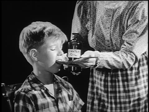 b/w 1962 woman feeding castor oil in spoon to boy who makes face of disgust - disgust stock videos & royalty-free footage