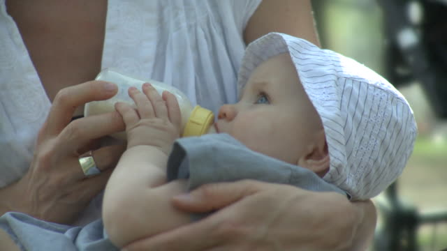 stockvideo's en b-roll-footage met cu woman feeding daughter (6-11 months), outdoors, new york city, new york, usa - zuigfles