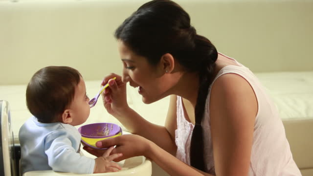 woman feeding her baby  - füttern stock-videos und b-roll-filmmaterial