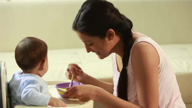woman feeding her baby  - familie mit einem kind stock-videos und b-roll-filmmaterial