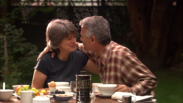 vidéos et rushes de woman feeding man seated at outdoor table / man and woman kissing on lips / woman serving man and herself granola - quinquagénaire