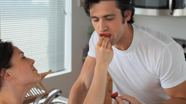 ms  woman feeding man strawberry in kitchen, jersey city, new jersey, usa - füttern stock-videos und b-roll-filmmaterial