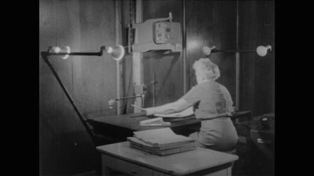 1960 woman feeds census forms through a microfilm scanner - census stock videos & royalty-free footage