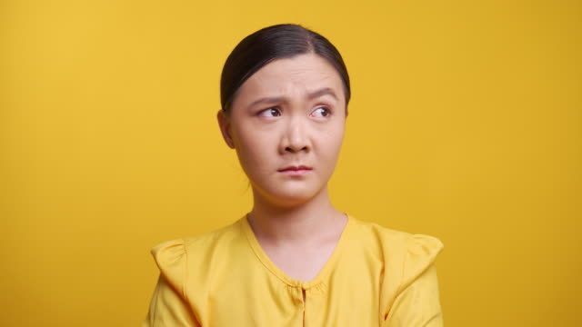 woman feel confused isolated over yellow background - uncertainty stock videos & royalty-free footage