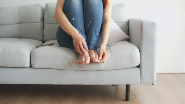 女性はリビングルームでかゆい足を感じる - 悪臭点の映像素材/bロール