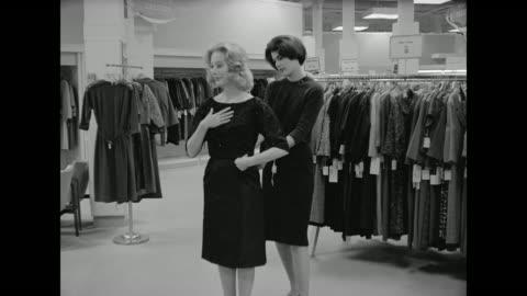 vídeos y material grabado en eventos de stock de 1962 a woman feels she's not alone while trying on a dress at a department store - gran almacén