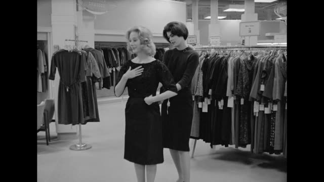 vídeos de stock e filmes b-roll de 1962 a woman feels she's not alone while trying on a dress at a department store - cabine de loja