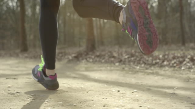 Woman feet and legs running in slow motion with flares