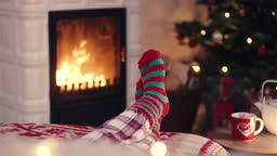 Woman feet in cozy christmas woolen socks near fireplace with decorated xmas tree and tee cup in background