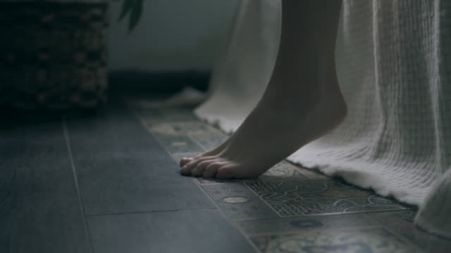 Woman feet touching floor in the morning