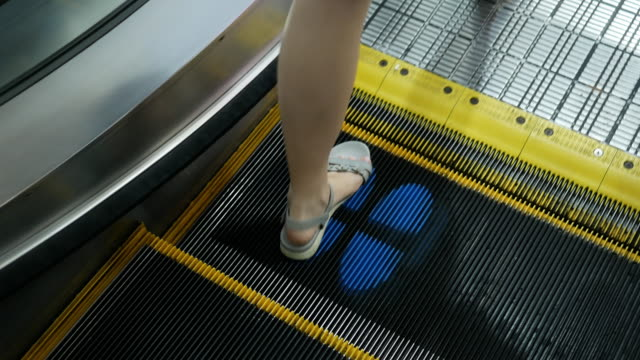 pov , woman feet walking down on escalator , covid-19 business signage on floor , new normal concept - footprint stock videos & royalty-free footage