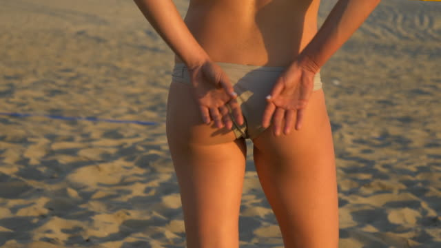 a woman female beach volleyball player shows a sign to her partner behind her butt back. - slow motion - volleyballnetz stock-videos und b-roll-filmmaterial