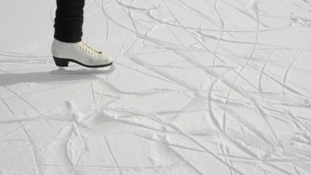 vídeos y material grabado en eventos de stock de woman figure skates onto frozen pond below mountains - pista de hielo