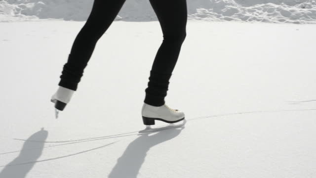 Woman figure skates onto frozen pond below mountains