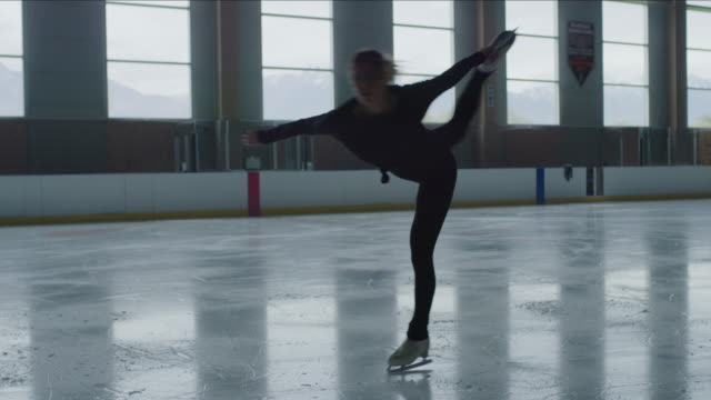woman figure skating on ice skating rink while holding leg raised / murray, utah, united states - figure skating stock videos & royalty-free footage