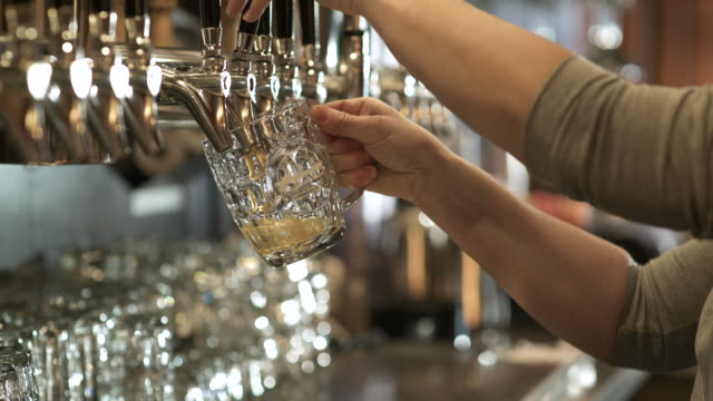 woman filling a glass with beer from a tap - beer stein stock videos and b-roll footage