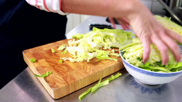 woman filling chopped cabbage into chinese bowl - schneiden stock videos & royalty-free footage